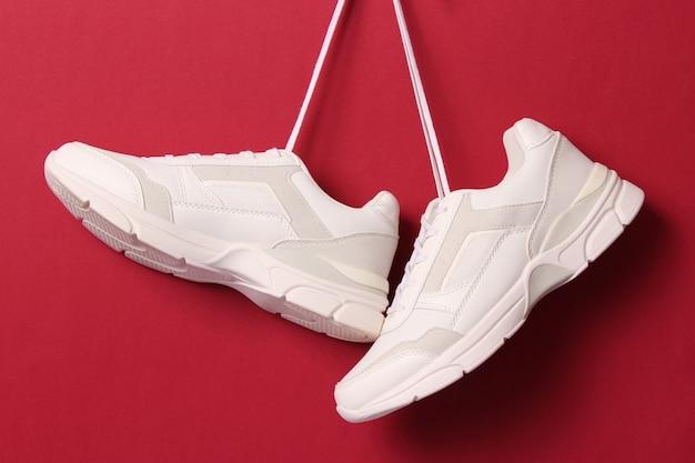 Le moderne sneakers alla moda si appendono ai lacci su uno sfondo colorato