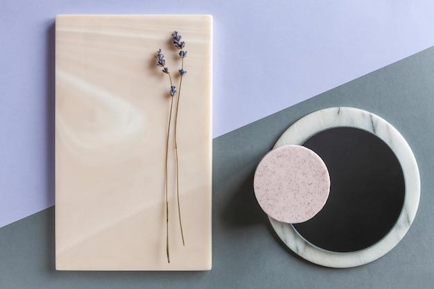 Moderna spa e concetto di benessere alla moda con sapone alla lavanda su piatti di pietre naturali.