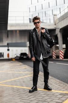 Moderno e alla moda giovane hipster in abiti giovanili di moda neri in occhiali da sole vintage con uno zaino elegante si erge per strada in una giornata primaverile. ragazzo americano all'aperto. abbigliamento e accessori per uomo.