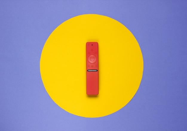 Telecomando moderno per tv in custodia su carta colorata con cerchio giallo al centro