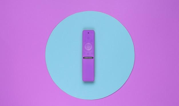 Telecomando moderno della tv nel mezzo di sfondo rosa con cerchio blu. vista dall'alto