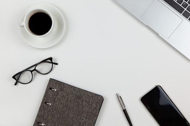 Moderno spazio di lavoro unisex, vista dall'alto. blocco note, penna, caffè, smartphone, occhiali, computer portatile su sfondo bianco, copia spazio, piatto laici
