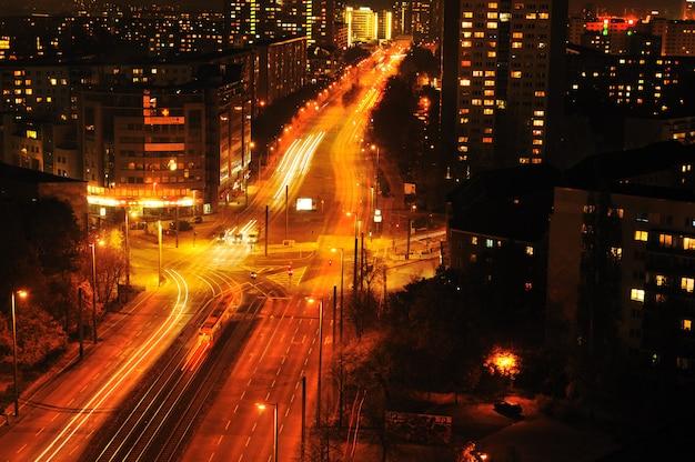 Città urbana moderna alla notte con traffico dell'autostrada
