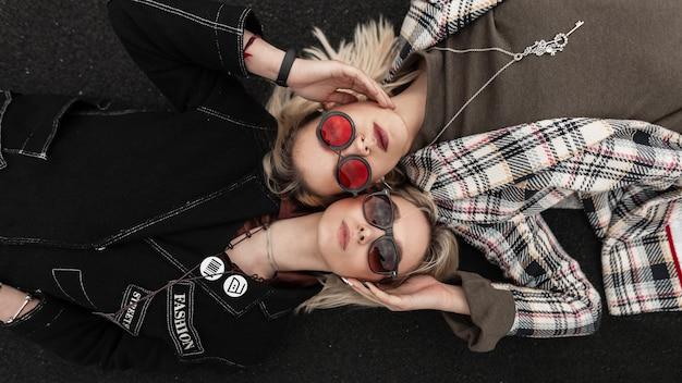 Giovani sorelle urbane moderne ed eleganti in occhiali alla moda in vestiti alla moda per giovani che riposano sulla strada. ritratto fresco due bionde sexy belle amiche sulla strada