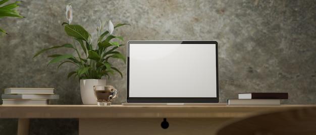 Luogo di lavoro vintage moderno con mockup di schermo vuoto del computer portatile sulla tavola di legno nella parete del sottotetto del cemento di lerciume