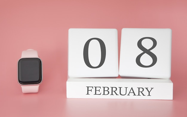 Orologio moderno con calendario cubo e data 08 febbraio su sfondo rosa. vacanze invernali di concetto.