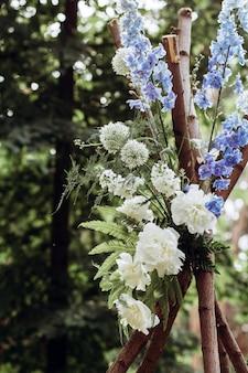 Un moderno arco nuziale per una cerimonia all'aperto decorato con fiori bianchi e blu