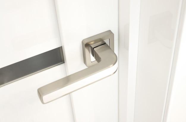 Porta moderna bianca con maniglia cromata. concetto di mobili.