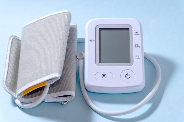 Tonometro elettrico bianco moderno su un primo piano blu del fondo. un dispositivo per misurare la pressione.