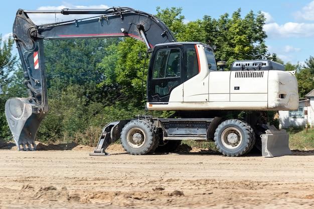 Escavatore bianco moderno in piedi su una scavatrice a terra con un lavoro stradale della benna su un'autostrada interurbana