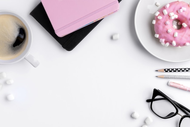 Tavolo da ufficio moderno bianco da ufficio con blocco note, penne e tazza di caffè