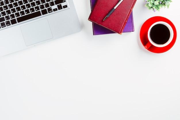 Tavolo da ufficio moderno bianco con laptop, penna, taccuino e tazza di caffè. vista dall'alto con co