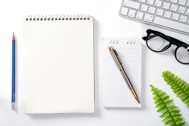 Moderna scrivania bianca con taccuino tastiera vista dall'alto con spazio copia piatto.