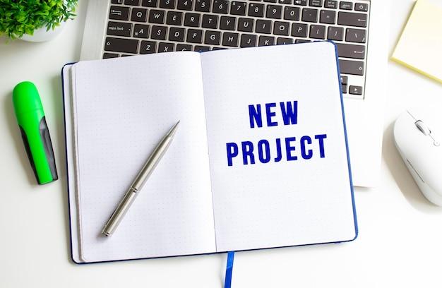 Scrivania da ufficio moderna bianca con laptop e altri accessori. blocco note con il testo nuovo progetto.