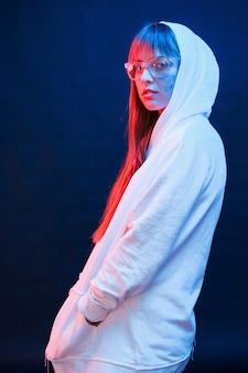 Nel moderno abbigliamento bianco. studio girato in studio scuro con luce al neon. ritratto di giovane ragazza