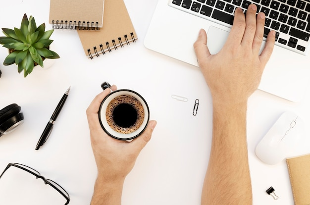 Area di lavoro bianca moderna con laptop, mani maschili, album da disegno e tazza di tè