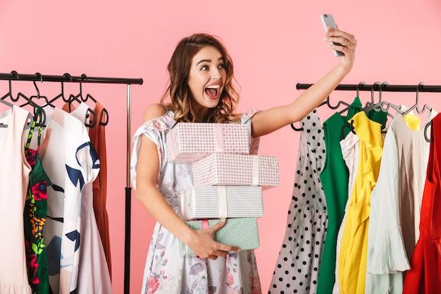 Donna moderna con acquisto in piedi in negozio vicino a stendibiancheria e tenendo selfie sul cellulare isolato in rosa