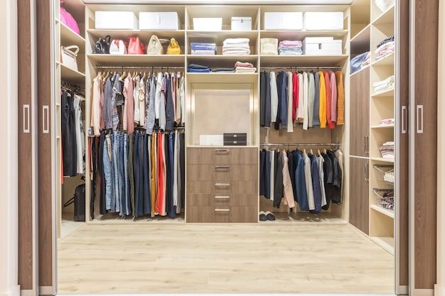 Guardaroba in legno moderno con vestiti appesi su rotaia in cabina armadio interno di design