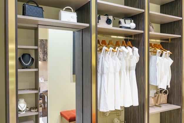 Armadio in legno moderno con vestiti appesi su rotaia in cabina armadio interior design