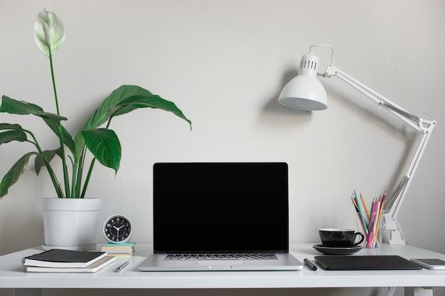 Tavolo da lavoro moderno con computer portatile vuoto e accessori in ufficio a casa