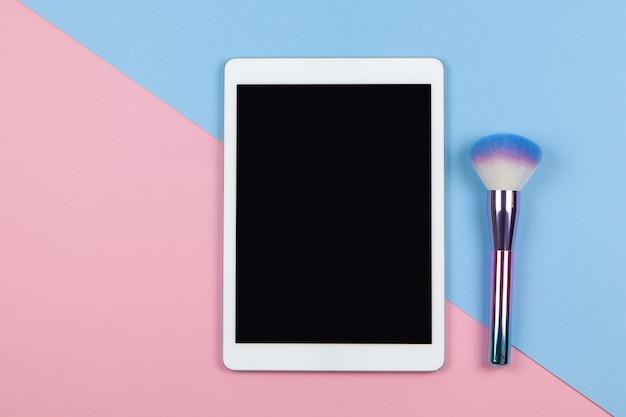 Spazio di lavoro moderno di visagiste, vista dall'alto. tablet, pennello trucco su sfondo bicolore
