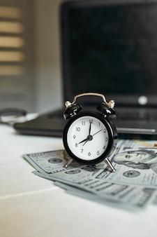 Posto di lavoro moderno di laptop, orologio, denaro, banconote in dollari con spazio di copia su fondo di legno bianco. tempo per soldi.