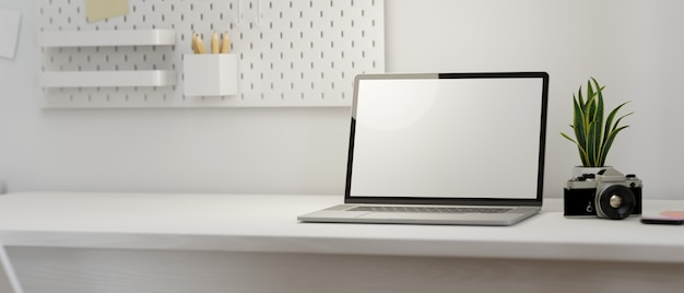 Modello moderno del posto di lavoro con lo schermo in bianco del computer portatile e spazio vuoto sulla rappresentazione bianca della tavola 3d