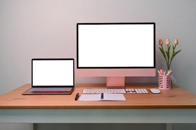 Posto di lavoro moderno con computer, laptop e forniture sulla scrivania in legno.