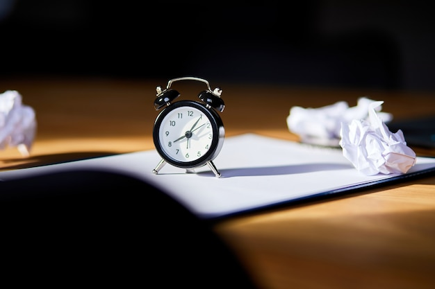 Luogo di lavoro moderno, scrivania in legno in piena luce, luce solare con orologio, foglio di carta, laptop, notebook, palline di carta stropicciata, change your mindset, piano b, tempo per fissare nuovi obiettivi, business