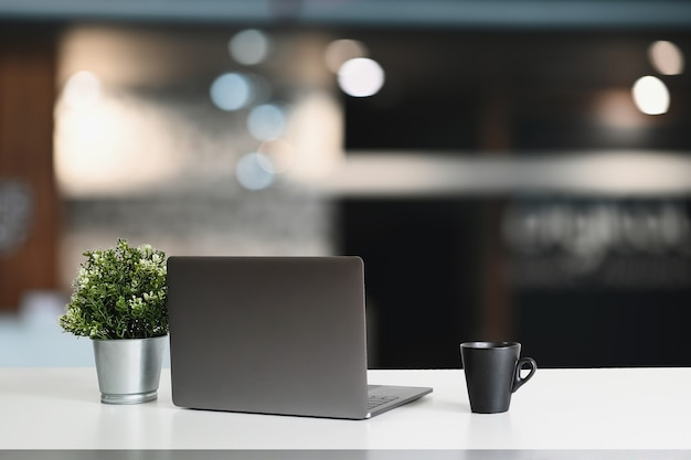 Area di lavoro moderna con computer portatile e decorazioni sul tavolo bianco.