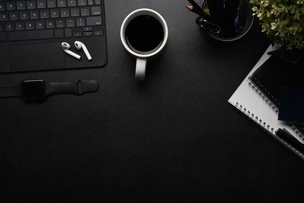 Area di lavoro moderna con auricolari ireless, smart watch, notebook, tastiera wireless e spazio per le copie.