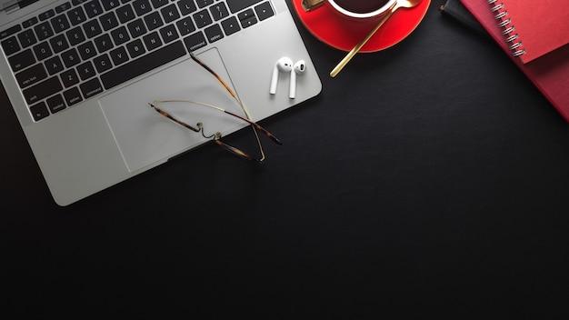 Area di lavoro moderna con laptop, tazza di caffè e forniture per ufficio su tablet nero con spazio di copia