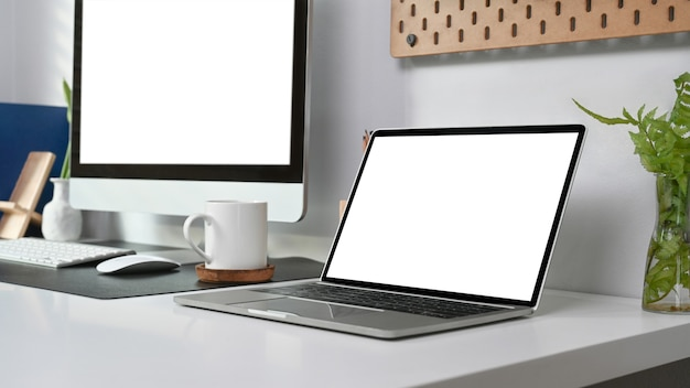 Area di lavoro moderna con laptop, computer, tazza di caffè e pianta d'appartamento in ufficio a casa.