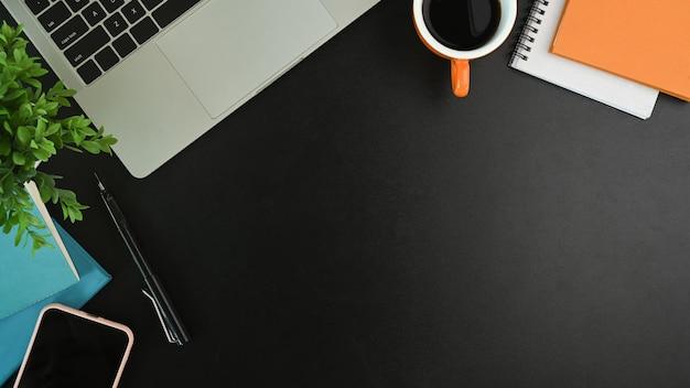Area di lavoro moderna con laptop, smartphone, tazza di caffè, notebook e pianta sul tavolo nero.