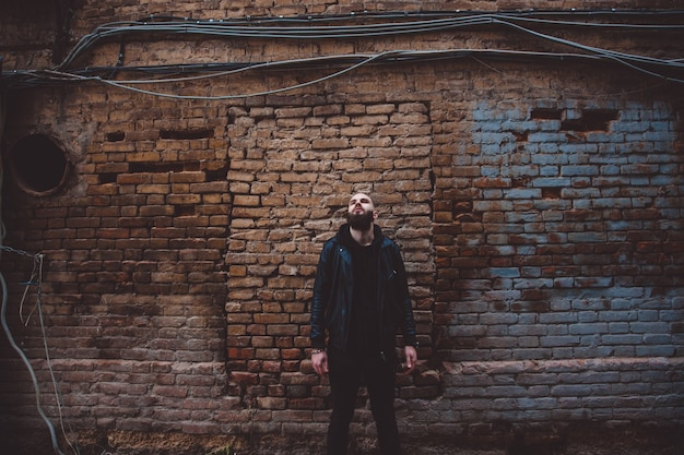 Moderno giovane uomo barbuto in vestiti di stile nero in posa contro il muro di mattoni.