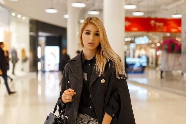 Modello moderno della giovane donna bionda in un cappotto alla moda chic Foto Premium