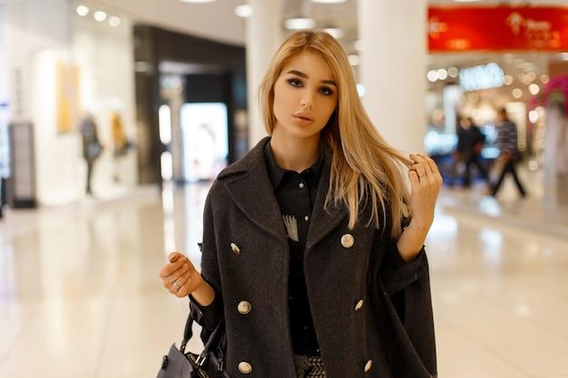 Modello moderno della giovane donna bionda in un cappotto alla moda chic