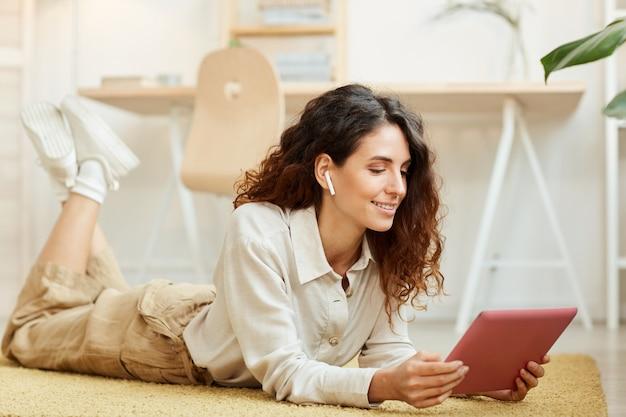 Moderna giovane imprenditrice sdraiato sul pavimento mentre si ascolta i suoi colleghi durante la conferenza online