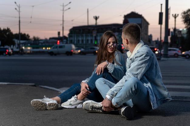 Le giovani coppie moderne si siedono sulla strada sullo sfondo della città di sera. una ragazza e un ragazzo sistemano le cose per strada.