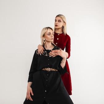 Moderna giovane modella di moda in abiti vintage alla moda in piedi uno accanto all'altro nella stanza