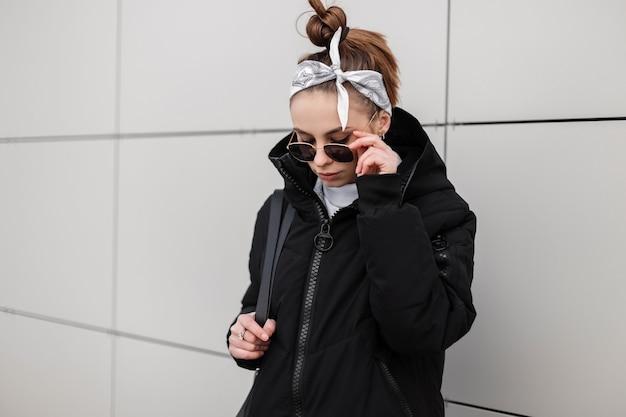 Donna moderna giovane hipster con acconciatura alla moda in una bandana in una giacca nera alla moda con uno zaino alla moda in un golf lavorato a maglia in occhiali da sole alla moda in posa vicino a un edificio bianco. ragazza alla moda.