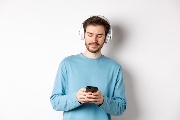 Giovane moderno in felpa blu ha messo su musica su smartphone, ascoltando canzoni in cuffie senza fili, sfondo bianco.