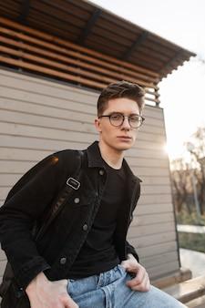 Il giovane moderno in giacca nera di jeans in jeans vintage blu con gli occhiali si siede vicino a un edificio in legno sulla strada