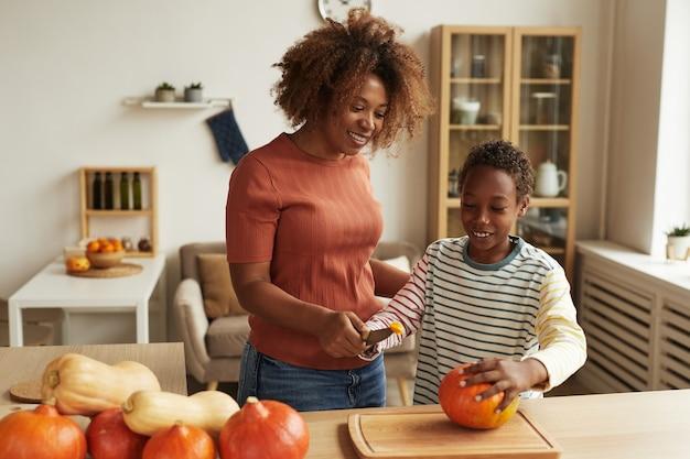 Moderna giovane madre e il suo bambino in piedi insieme al tavolo iniziando a intagliare zucche per halloween