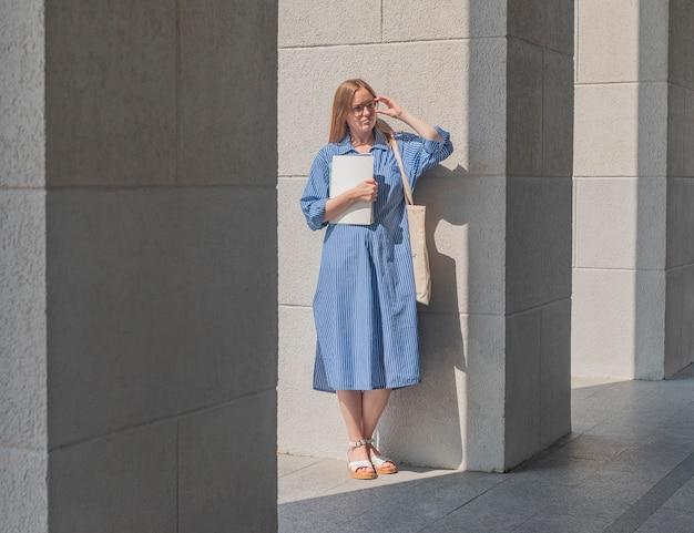 Giovane studente moderno in occhiali in piedi vicino a colonne universitarie con libri e libri di testo