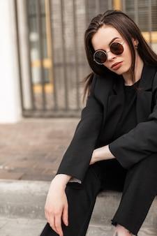 La giovane donna moderna in blazer alla moda in maglietta alla moda si siede in città. il modello alla moda della ragazza in vestiti alla moda neri riposa sulla piastrella dell'annata sulla via. abbigliamento alla moda per le donne.