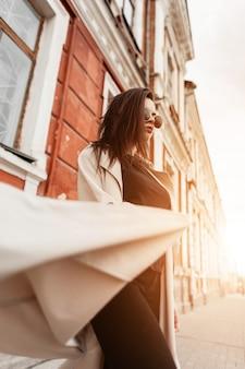 Giovane donna moderna in occhiali da sole alla moda in abiti casual neri in trench beige primaverile in posa sulla strada vicino all'edificio al tramonto. il modello attraente della ragazza gode della passeggiata e della luce solare intensa arancione.