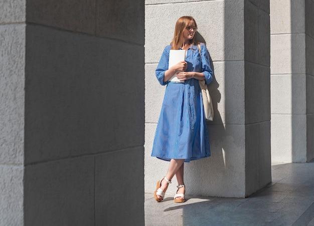 Giovane donna moderna in occhiali in piedi vicino a colonne universitarie con libri accademici e guardando un...