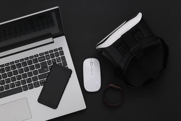 Gadget e dispositivi per giovani moderni su sfondo nero. vista dall'alto. lay piatto