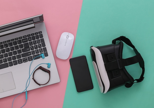 Gadget e dispositivi per giovani moderni su sfondo blu rosa. vista dall'alto. lay piatto